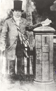 Postman with pillar box, late 1850s